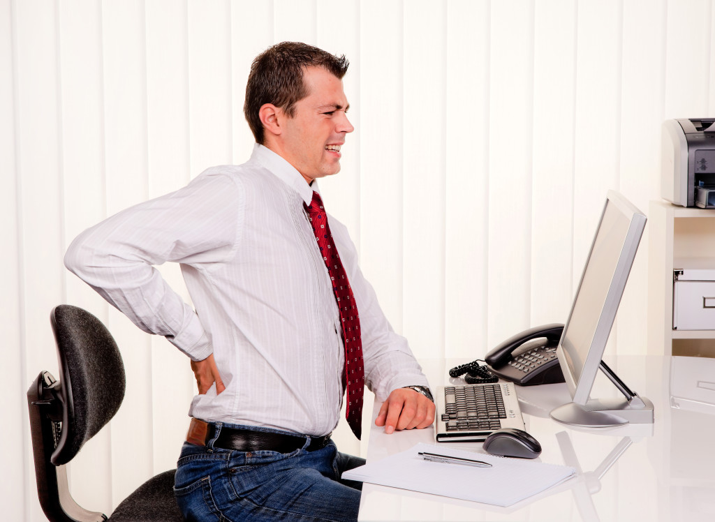 Young man in office with computer and back pain