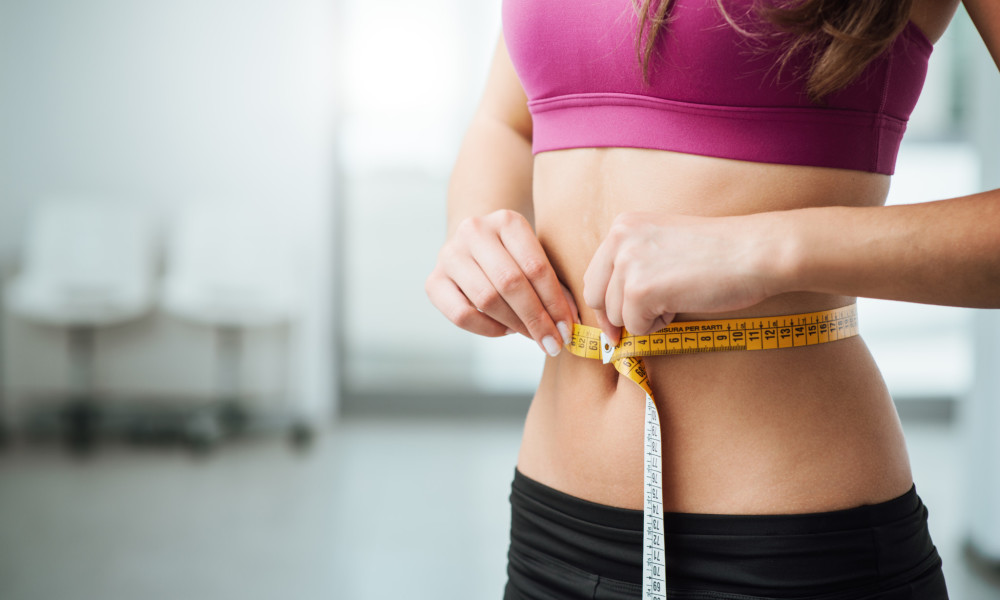 Slim young woman measuring her thin waist with a tape measure close up ** Note: Shallow depth of field